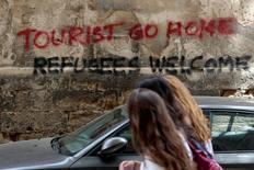 People walk past a graffiti in Palma de Mallorca, in the Spanish island of Mallorca, May 23, 2016. REUTERS/Enrique Calvo