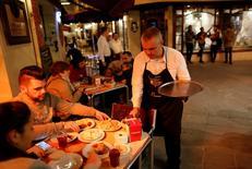 Los sectores de transporte, comercio, hostelería y entretenimiento generarán más de 480.000 empleos temporales durante la campaña veraniega gracias al tirón del turismo, dijo el lunes la empresa de trabajo temporal Randstad. En la imagen, un camarero sirve comida en Sevilla, el 4 de marzo de 2016. REUTERS/Marcelo del Pozo