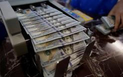 Банковский служащий пересчитывает доллары. Доллар слабо вырос к корзине основных валют во вторник после того, как экономические данные не поддержали ожидания повышения процентной ставки Федрезервом в июне или июле. REUTERS/Kham