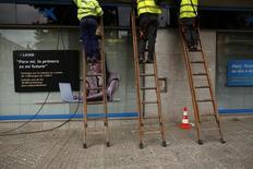 Los grupos de telefonía móvil que operan en la ciudad de Madrid deberán pagar al Ayuntamiento un total de 33,7 millones de euros por una tasa que grava el uso del suelo y subsuelo público. Imagen de trabajadores instalando cables de fibra óptica en Sevilla el 17 de diciembre de 2013. REUTERS/Marcelo del Pozo