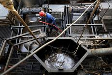 The flow of drilling mud is seen in a container while an oilfield worker works on a drilling rig at an oil well operated by Venezuela's state oil company PDVSA, in the oil rich Orinoco belt, near Cabrutica at the state of Anzoategui April 16, 2015. REUTERS/Carlos Garcia Rawlins/File Photo
