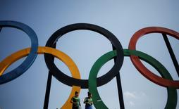 Brazilian badminton players Lohaynny Vicente (L), 20, and her sister Luana Vicente, 22, stand under a set of Olympic rings installed at Madureira Park in Rio de Janeiro, Brazil, May 4, 2016. REUTERS/Nacho Doce