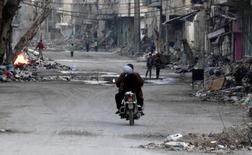 A man and a woman ride a motorcycle along a street filled with debris of damaged buildings in Deir al-Zor March 5, 2014. Picture taken March 5, 2014. REUTERS/Stringer