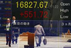 Люди проходит мимо экрана, показывающего котировки индекса Nikkei в Токио 19 апреля 2016 года. Японский фондовый рынок восстановился по итогам торгов вторника, отступив от минимума четырех недель, после того как глава ФРС США Джанет Йеллен в ходе своего выступления в понедельник воздержалась от прямых указаний, когда будет поднята процентная ставка, хотя и не исключила, что это произойдет в скором времени. REUTERS/Thomas Peter