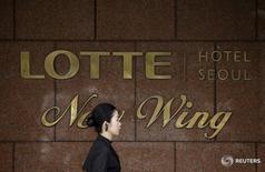 Женщина проходит мимо логотипа Lotte Hotel на стене отеля компании в Сеуле 25 марта 2016 года. Южнокорейская Hotel Lotte Co Ltd сократила объем планируемого первичного размещения акций, которое теперь оценивается до 5,26 триллиона вон ($4,56 миллиарда), и заявила, что расследование в отношении директора компании может повлиять на весь бизнес. REUTERS/Kim Hong-Ji/File Photo