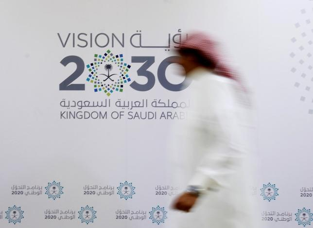 A Saudi man walks past the logo of Vision 2030 after a news conference in Jeddah, Saudi Arabia June 7, 2016. REUTERS/Faisal Al Nasser