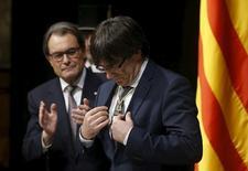 El presidente de la Generalitat catalana, Carles Puigdemont comunicó el miércoles a su grupo parlamentario que da por roto el acuerdo de estabilidad firmado por la CUP después de que la formación antiausteridad decidiese mantener una enmienda a la totalidad de los presupuestos regionales. En la imagen, Carles Puigdemont mira una medalla recibida del anterior presidente catalán, Artur Mas (izquierda), durante la toma de posesión de Puigdemont como presidente de la Generalitat de Catalunya en el Palau de la Generalitat en Barcelona, 12 de enero de 2016. REUTERS/Albert Gea