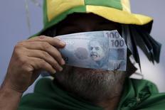Демонстрант  в Бразилиа 13 марта 2016 года держит в руках бумаги, имитирующие банкноты. REUTERS/Ueslei Marcelino