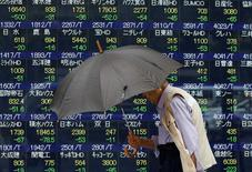 El principal índice de las bolsas europeas caía el lunes a su nivel más bajo en un mes, reproduciendo las pérdidas en los mercados asiáticos y estadounidenses, al presionar a la baja el retroceso del sector energético. En la imagen, una persona con un paragüas pase delante de unas pantallas con cotizaciones en Tokio, Japón, 13 de junio de 2016. REUTERS/Issei Kato