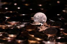 Рублевые монеты. 7 июня 2016 года. Банк России полагает, что давление на курс рубля в мае могли оказать в том числе операции иностранных банков по продаже форвардных контрактов на валютную пару доллар-рубль своим клиентам-нерезидентам, желающим таким образом захеджировать курсовые риски по предстоящим в ближайшие месяцы (и анонсированным в мае) дивидендным выплатам по акциям российских компаний. REUTERS/Maxim Zmeyev/Illustration