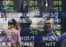 Personas se reflejan en un tablero electrónico que muestra información bursátil, en una correduría en Tokio, Japón. 18 de abril de 2016. Las bolsas de Asia operaban volátiles el miércoles antes de una decisión de política monetaria de la Reserva Federal de Estados Unidos más tarde en el día y por el temor a una posible salida del Reino Unido de la Unión Europea. REUTERS/Toru Hanai