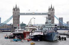 """Les partisans du Brexit ont déployé mercredi sur la Tamise une flottille de chalutiers décorés d'Union Jack et de banderoles colorées en espérant s'attirer le soutien des électeurs britanniques à huit jours du référendum sur l'avenir du Royaume-Uni dans l'Union européenne. Les partisans du """"Remain"""" ont à leur tour manifesté leur désaccord en déroulant des banderoles floquées du """"In"""" sur le Tower Bridge et les quais. /Photo prise le 15 juin 2016/REUTERS/Stefan Wermuth"""