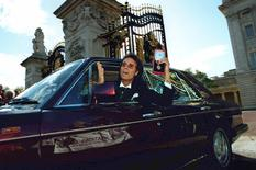 Pop star Cliff Richard shows off his medal as he leaves Buckingham Palace after picking up his knighthood from the Queen, in London, Britain October 25, 1995. REUTERS/Dylan Martinez