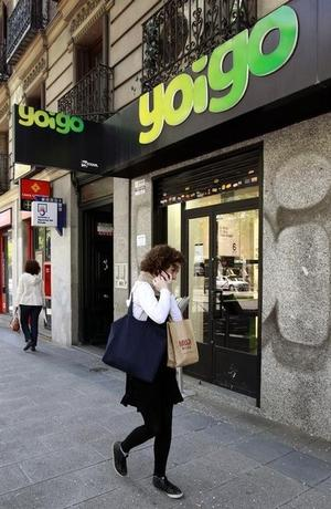 A woman speaks on her mobile phone as she walks past a Yoigo shop in Madrid, April 26, 2011.  REUTERS/Andrea Comas