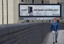 Un hombre camina cerca de un cartel de la campaña por la permanencia del Reino Unido en la Unión Europea, en Londres. 21 de junio de 2016. A dos días de un referendo sobre la membresía de Reino Unido a la Unión Europea que dará forma al futuro del bloque y de Occidente, los sondeos indicaban que la opinión británica está tan dividida que el resultado es aún incierto. REUTERS/Toby Melville