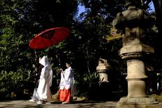 A couple walk in the garden of the Hikawa shrine during their traditional Shinto wedding ceremony in Tokyo December 1, 2015.  REUTERS/Thomas Peter