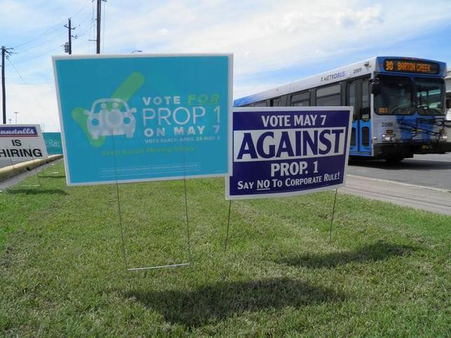 Campaign signs concerning a municipal vote over fingerprint requirements for ride-hailing companies such as Uber and Lyft are seen along a roadway in Austin, Texas, May 6, 2016. REUTERS/Jon Herskovitz/File Photo
