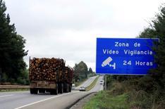 Un camión forestal transita en la región de la Araucanía cerca de una señal que avisa de vigilancia por video, cerca de Ercilla en el sur de Chile. 7 de junio de 2016. REUTERS/Gram Slattery