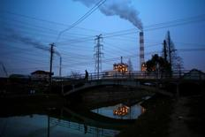 A man walks over a bridge as smoke rises from chimneys of a thermal power plant in Shanghai February 23, 2015. REUTERS/Carlos Barria/File Photo