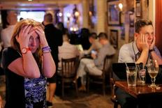 People gathered in The Churchill Tavern, a British themed bar, react as the BBC predicts Briatin will leave the European Union, in the Manhattan borough of New York, U.S., June 23, 2016.  REUTERS/Andrew Kelly