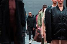El rapero Kanye West pasa entre unas modelos tras presentar su colección otoño/invierno 2015 con Adidas en la Semana de la Moda de Nueva York, feb 12, 2015. Adidas acordó ampliar su colaboración con el rapero Kanye West, que incluye la apertura de nuevas tiendas, con la expectativa de aumentar la notoriedad que ha ganado en el mercado de Estados Unidos desde que en 2013 arrebató a Nike el patrocinio que tenía con el cantante devenido en diseñador.      REUTERS/Lucas Jackson/File photo