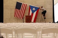 Un trabajador retira las banderas de Estados Unidos y Puerto Rico tras una conferencia en San Juan, Puerto Rico. 16 de mayo de 2016. Un plan de alivio financiero para que Puerto Rico pueda pagar su deuda de 70.000 millones de dólares superó el miércoles una importante barrera en el Senado de Estados Unidos, al obtener la mayoría necesaria para que el asunto sea debatido y pase a una votación final posiblemente esta semana. REUTERS/Alvin Baez