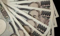 Банкноты по 10000 иен. Токио, 2 августа 2011 года. Слабая экономика, дефляция, внушительный госдолг, отрицательные процентные ставки и стареющее население не кажутся хорошими поводами для роста национальной валюты, однако это именно то, что происходит с японской иеной после решения Великобритании проголосовать за выход из Евросоюза. REUTERS/Yuriko Nakao/File Photo