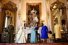 Exhibition curator Caroline de Guitar poses for photographers as she shows off a preview of an exhibition entitled 'Fashioning a Reign: 90 Years of Style from The Queen's Wardrobe,' charting the reign of Britain's Queen Elizabeth through a display of her formal and informal outfits, at Buckingham Palace, in central London, Britain July 4, 2016.    REUTERS/Dylan Martinez