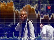 Un hombre se refleja en una pantalla que muestra información bursátil, afuera de una correduría en Tokio, Japón. 27 de junio de 2016. Las bolsas de Asia dejaban atrás unas pérdidas iniciales y subían el lunes, y la presión sobre el dólar de Australia se reducía luego de que Moody's minimizó la incertidumbre en el país después de las elecciones del fin de semana. REUTERS/Toru Hanai
