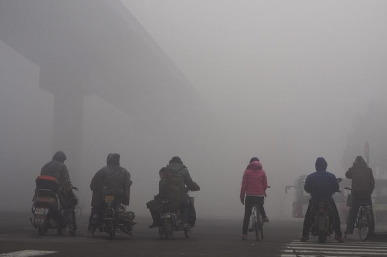 Residents on their bicycles and electric bikes wait for the traffic at an intersection amid heavy smog in Shijiazhuang, Hebei province, China, December 10, 2015. REUTERS/Stringer