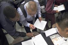 Personas buscando empleo rellenan formularios en una feria de trabajos en Los Ángeles, California. 4 de junio de 2015. El número de estadounidenses que presentaron nuevas solicitudes de subsidios por desempleo cayó inesperadamente la semana pasada, lo que confirma aún más que el mercado laboral permanece sólido, pese al débil aumento de las contrataciones en mayo. REUTERS/David McNew