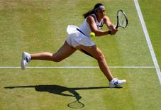 Marion Bartoli of France hits a return to Sabine Lisicki of Germany during their women's singles final tennis match at the Wimbledon Tennis Championships, in London July 6, 2013.  REUTERS/Adrian Dennis