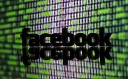 Напечатанный на 3D-принтере логотип Facebook на фоне двоичного кода. 22 марта 2016 года. Группа израильтян и американцев, потерявших родственников в результате палестинских атак, сообщила в понедельник, что будет требовать $1 миллиард в качестве компенсации от Facebook Inc, которую считает причастной к их смерти, следует из иска, поданного против социальной сети в США. REUTERS/Dado Ruvic/Illustration