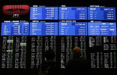 Посетители Токийской фондовой биржи у экрана с рыночными котировками. 9 февраля 2016 года. Японский индекс Nikkei вырос во вторник на фоне улучшения настроений инвесторов в связи с падением иены и надеждами на новые меры господдержки экономики. REUTERS/Issei Kato