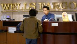 FILE PHOTO --  Bank Teller Tyler Wong talks to a customer at the Wells Fargo bank in Denver, Colorado, U.S. April 13, 2016.  REUTERS/Rick Wilking/File Photo