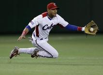 Cuba's third baseman Yulieski Gurriel catches the ball hit by Taiwan's Yang Dai-Kang in the first inning at the World Baseball Classic (WBC) second round game in Tokyo March 9, 2013. REUTERS/Toru Hanai