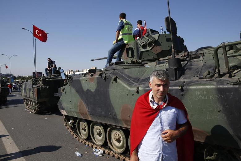 A man wrapped in a Turkish flag stands next to military vehicles in front of Sabiha Airport, in Istanbul, Turkey July 16, 2016. REUTERS/Baz Ratner