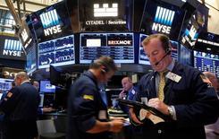 Трейдеры на фондовой бирже в Нью-Йорке. 18 июля 2016 года. Фондовые индексы США слегка повысились по итогам торгов понедельника, при этом индексы S&P 500 и Dow Jones зафиксировали новые рекордные максимумы, чему способствовали превзошедшие ожидания финансовые результаты Bank of America и рост акций технологических компаний. REUTERS/Brendan McDermid