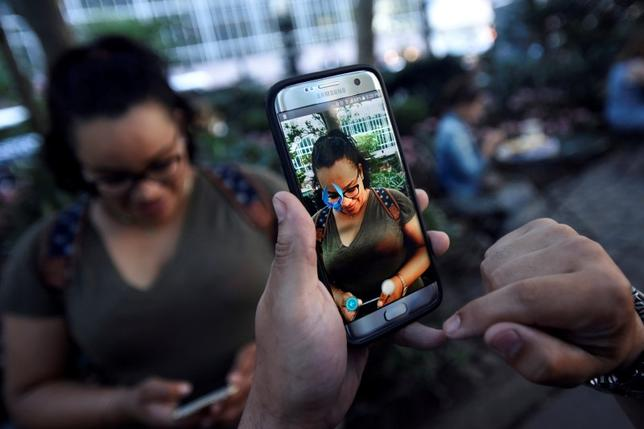 A Pokemon appears on the screen next to a woman as a man plays the augmented reality mobile game ''Pokemon Go'' by Nintendo in Bryant Park in New York City, U.S. July 11, 2016. REUTERS/Mark Kauzlarich/File Photo