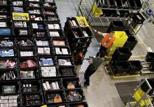 El gigante mundial de comercio electrónico Amazon recrudeció el miércoles la competencia en la distribución online al anunciar que ha incorporado un servicio de entrega en una hora en Madrid capital y otros 21 puntos de la región, añadiendo por primera vez en España la posibilidad de adquirir productos frescos. En la imagen, varias personas trabajan en un almacén de Amazon en Madrid, el 24 de noviembre de 2015.  REUTERS/Andrea Comas