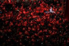 Сторонники президента Турции Тайипа Эрдогана размахивают национальными флагами во время демонстрации на площади Таксим в Стамбуле. 18 июля 2016 года. Военные перевороты редко помогают бизнесу, но представители как минимум одного небольшого сектора турецкой экономики переживают расцвет после провала путча 15 июля. REUTERS/Alkis Konstantinidis/File Photo