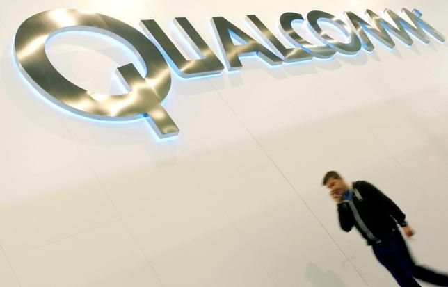 A man walks past a Qualcomm advertising logo at the Mobile World Congress at Barcelona, February 27, 2013. REUTERS/Albert Gea/File Photo     GLOBAL BUSINESS WEEK AHEAD PACKAGE - SEARCH ''BUSINESS WEEK AHEAD JULY 18'' FOR ALL IMAGES