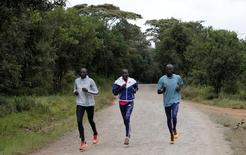 Athletes from South Sudan, part of the refugee athletes qualified for the 2016 Rio Olympics, (L-R) Paulo Amotun Lokoro of 1500m, Rose Nathike Lokonyen of 800m, Yiech Pur Biel of 800m, run along a dusty road during a training session at their camp in Ngong township near Kenya's capital Nairobi, June 9, 2016. REUTERS/Thomas Mukoya