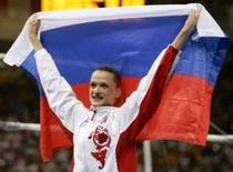 Russia's Svetlana Khorkina celebrates with her national flag after the women's artistic gymnastics individual all-round final at the Athens 2004 Olympic Summer Games August 19, 2004. RTXMUHJ