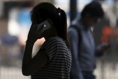 Foto de archivo de una mujer hablando por un celular iPhone, en Shanghái. 10 de septiembre de 2013. Apple Inc reportó el martes que las ventas de su icónico iPhone disminuyeron por segundo trimestre consecutivo, aunque la caída del 15 por ciento fue menor a lo que se temía. REUTERS/Aly Song/File Photo