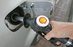 Водитель заправляет автомобиль на бензозаправочной станции в Англии. Royal Dutch Shell в четверг отчиталась о падении квартальной прибыли более чем на 70 процентов, значительно хуже ожиданий аналитиков, из-за низких цен на нефть, слабой прибыли от переработки и роста затрат в связи с приобретением BG Group за $54 миллиарда.  REUTERS/Toby Melville  TM/SH