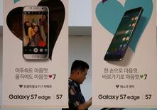 Un hombre camina detrás de avisos publicitarios de celulares Samsung, en Seúl. 28 de julio de 2016. El gigante surcoreano de tecnología Samsung Electronics dijo el jueves que espera seguir reportando sólidas ganancias en el segundo semestre del 2016, ya que la fuerte demanda de componentes probablemente compensaría la fuerte presión sobre los márgenes de sus teléfonos avanzados. REUTERS/Kim Hong-Ji