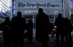 Люди в очереди на такси у редакции газеты New York Times в Нью-Йорке 7 февраля 2013 года. Американская медиакомпания The New York Times Co, владеющая одноименной газетой, зафиксировала квартальный убыток второй раз подряд из-за снижения продаж рекламы в печатных и цифровых источниках. REUTERS/Carlo Allegri
