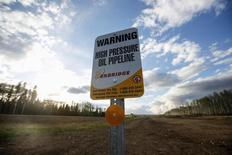 An Enbridge high pressure oil pipeline sign stands as smoke billows from the Fort McMurray in Kinosis, Alberta, Canada, May 5, 2016. REUTERS/Mark Blinch