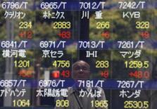 Un hombre se refleja en una pantalla que muestra información bursátil, en Tokio, Japón. 11 de julio de 2016. Las bolsas de Asia caían el viernes luego de tocar un máximo en cerca de un año, y el yen se fortalecía luego de que las nuevas medidas de estímulo anunciadas por el Banco de Japón decepcionaron a los inversores. REUTERS/Issei Kato